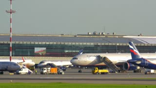 MOSCOW, RUSSIA - JULY 01, 2015: Panning shot of Sheremetyevo International Airport with many airplanes, moving trucks and terminal buildings on its territory
