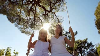 Mother and daughter are on a swing. Happy family is happy and enjoys