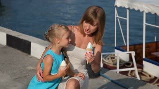 Mother and daughter eating ice cream. Daughter dabbles. Family looking at camera and smiling
