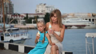 Mother and daughter eating ice cream on the pier near the water. Look at the camera and smiling
