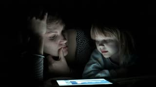 Mother and daughter enjoy the tablet at night