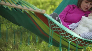 Mother and daughter lying in a hammock. Mom tells the tale