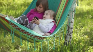 Mother and daughter lying in a hammock outdoors. They held mobile phones