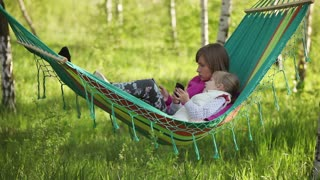 Mother and daughter lying in a hammock outdoors. They holding mobile phones