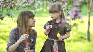 Mother and daughter playing in the park with bubbles