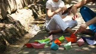 Mother and daughter playing with paper boats