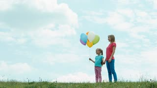 Mother and daughter with balloons against the sky. They looking at distance and smiling. Zooming
