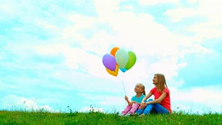 Mother and daughter with balloons sitting on the grass against the sky and playing with balloons
