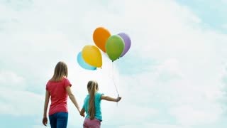 Mother and daughter with balloons turned and looking at the camera. Mother and daughter holding hands and looking at distance. Zooming
