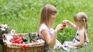Mother and daughter with vegetables outdoors. They hold tomatoes and looking at camera