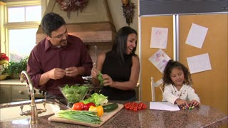 Mother and Father Making a Salad with Daughter
