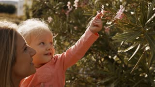Mother and little girl looking at flower on bush