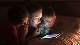 Mother and two children looking at tablet