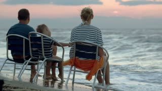 Mother, father and son sitting on chairs on beach at sunset. Dad showing something in the distance, boy kissing parents