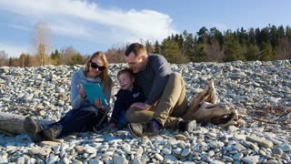 Mother, father and their little sit sitting on the stony shore. They talking and watching something on touchpad