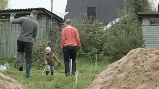 Mother, father and their little son having fun in the countryside. Parents dancing and boy playing with a long stick.