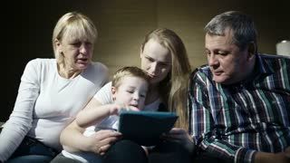 Mother, grandmother and granfather watching boy playing game on touchpad. Grandpa trying to help