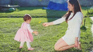 Mother is giving a flower to her baby daughter outdoors. Slow Motion 240 fps. Young mom and her cute little baby-girl are having fun in the sunny garden. Happy childhood concept. Young Family.