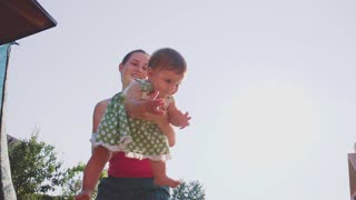 Mother is playing with her baby daughter outdoors. Slow Motion 240 fps. Young mom and her cute little baby-girl are having fun in the sunny garden. Happy childhood and motherhood concept. Young Family