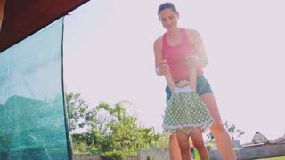 Mother is playing with her baby daughter outdoors. Slow Motion 240 fps. Young mom and her cute little baby-girl are having fun in the sunny garden. Happy childhood and motherhood concept.