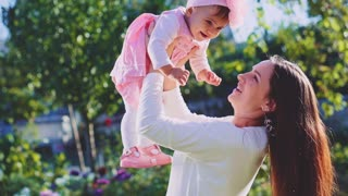 Mother is playing with her baby daughter outdoors. Slow Motion 250 fps. Young mom and her cute little baby-girl are having fun in the sunny garden. Happy childhood and motherhood concept. Young Family