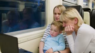 Mother, son and grandmother watching video on laptop in the train