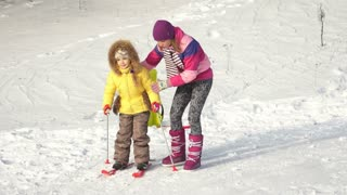 Mother teaching a child to ski