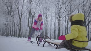 Mother throwing snow at her daughter, she is sitting on a sledge in the winter forest