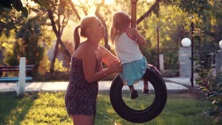 Mother twists the little daughter on a swing on backyard at home, in foreground and sunlight coming through trees