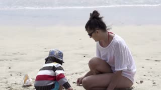 Mother with her son playing on the beach, slow motion shot at 60fps