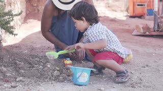 Mother with his son digging in the ground, slow motion shot at 240fps