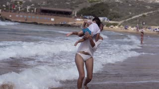 Mother with son running on the beach, slow motion shot at 240fps