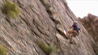 Mountain Climber Jumping Across the Face of a Mountain