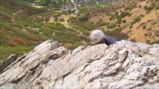 Mountain Climber Reaching the Top of an Outcropping of Rock
