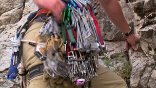 Mountain Climber Taking Camming Device and Putting It in Rock