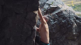 Movement stabilized shot of topless fearless climber ascending cliff with rope. Side view. He using carbines and long climbing rope. Rubbing his hands with chalk in sunlight