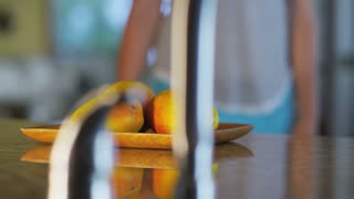 moving camera shot on fruit plate on kitchen counter, with woman