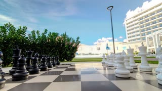 Moving outdoor big chess in the garden timelapse stop-motion play the famous game of chess without people