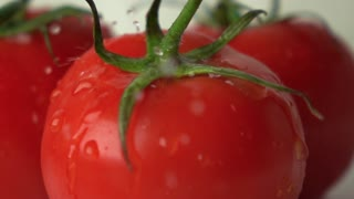 Multiple water drops hit red ripe tomato with green leaves super slow motion