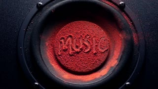 Music caption on orange powder over trembling loudspeaker. Super slow motion shot