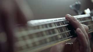Musician playing bass guitar at studio, close up, slow motion