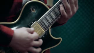Musician playing electric guitar at studio, close up, slow motion