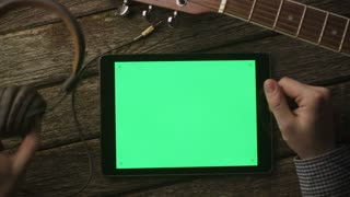 Musician Using Tablet PC with Green Screen in Landscape Mode. Top view. Causal Lifestyle