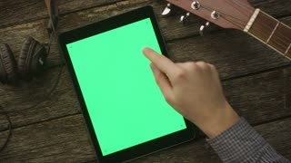 Musician Using Tablet PC with Green Screen in Portrait Mode. Top view. Causal Lifestyle