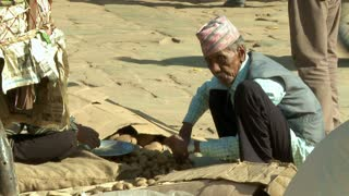 Nepali Man Sorts Through Nuts in Marketplace