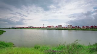 New cottage settlement Nekrasov village with reflection in lake in sunny summer day timelapse with clouds, Sochi, Russia