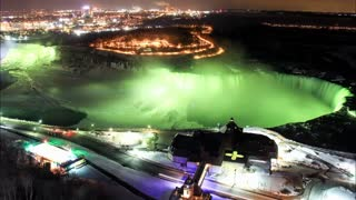 NIagara Falls Winter Night Time Lapse. Night time lapse shot of Niagara Falls as viewed from a highrise on the Canadian side looking at the American side. Shot during snowfall in winter, with changing colored light illumination. Tilting up.