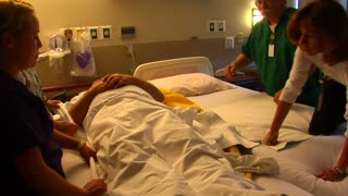 Nurses Moving Patient From One Bed To Another
