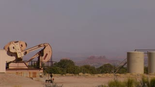 Oil Pump In Red Rock Desert With Tanks