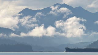 Oil Tanker Passing Cloudy Mountains